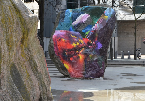 rock covered with a digital image, glued on it, outside, trees around