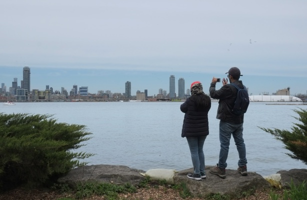 two people standing on the shore of Center Island, looking at the Toronto skyline and taking pictures of it.