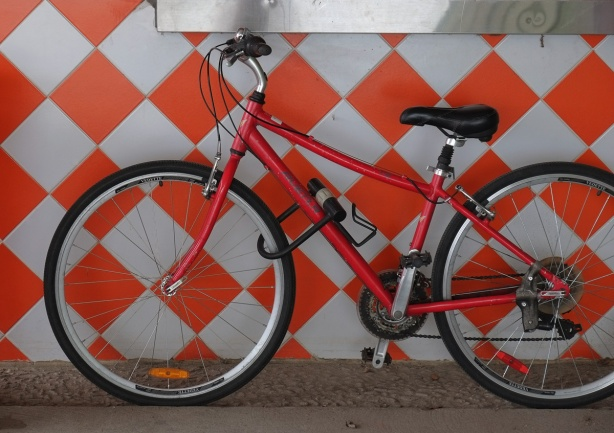 the orange and white wall tile pattern of Pizza Pizza with a red bike parked in front of it.