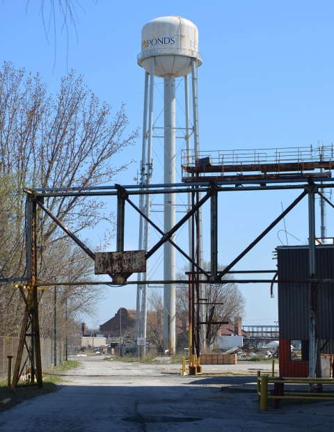 white water tower in the background with Ponds written on it, metal overhead structure for trucks entering old abandoned factory in the foreground with faded sign that once was warning speed bumps