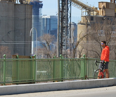 a man in orange stands beside his bike on the side of a road, sity in the background