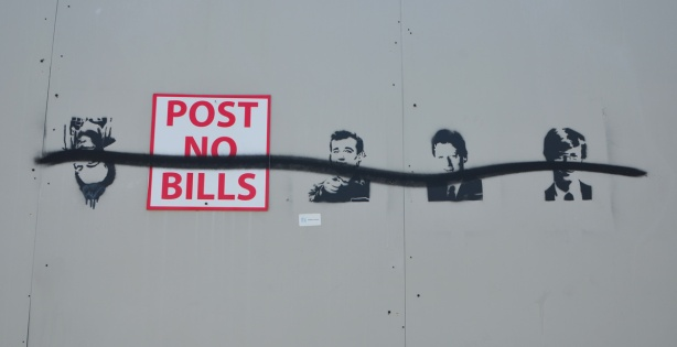 on grey construction hoardings, a sign tat says post no bills. Someone has added 4 stencils of different Bills, Bill Murray, Bill Clinton.