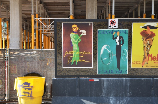 art deco posters on hoardings in front of a construction site