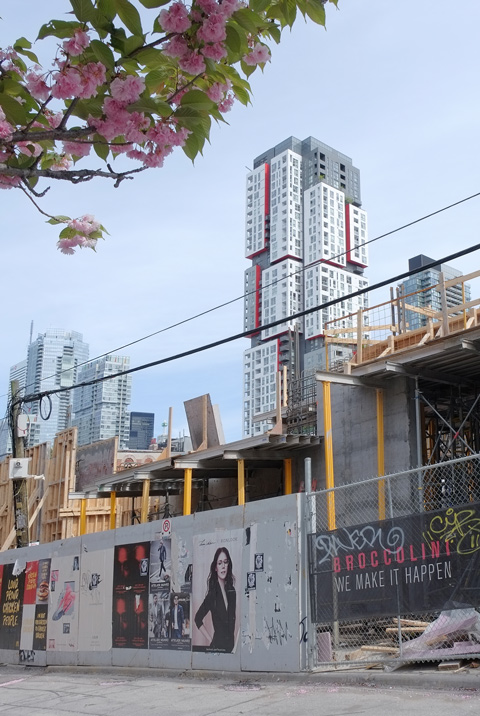 construction site, with posters on the hoardings, tall white, grey, and red building in the background.