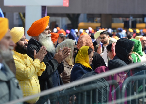 sihks in turbans and saris praying at a khalsa event outdoors