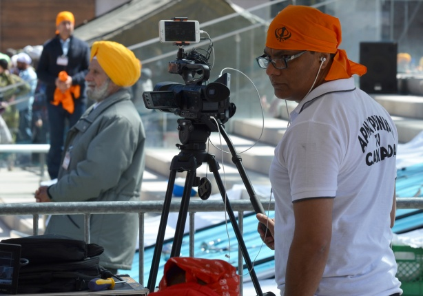 Under a tent covering, a man from Punjabi TV is filming khalsa prayers and celebration at Nathan Phillips square