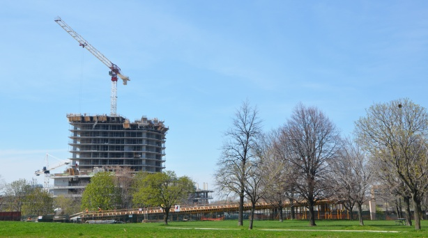 construction of an elevated ramp beside a park from a distance, with condo building going on behind it