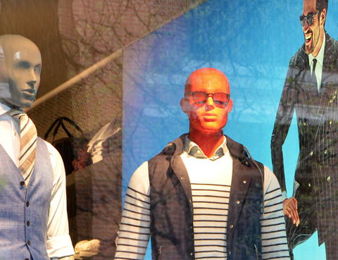 two male mannequins in a mens wear store window, one has a very red face, also a picture of a man in a black suit with a bright blue background is in the window