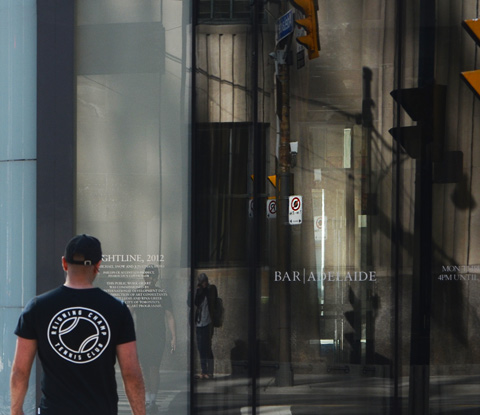 a man in a black tshirt crosses the street towards a large indow with lots of reflections in it.