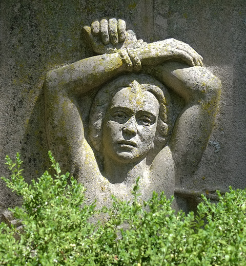 relief sculpture on a tombstone at mt pleasant cemetery, person with arms folded over top of head.