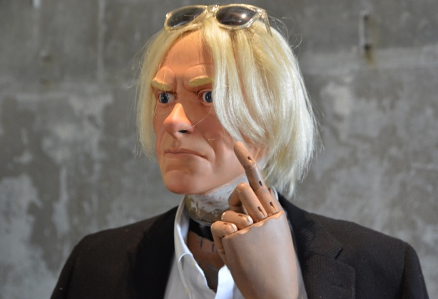 mannequin automatons as part of an art installation in the old Unilever soap factory, concrete floor and walls - the likeness of Andy Warhol, white hair, glasses on head, hand up, finger pointing