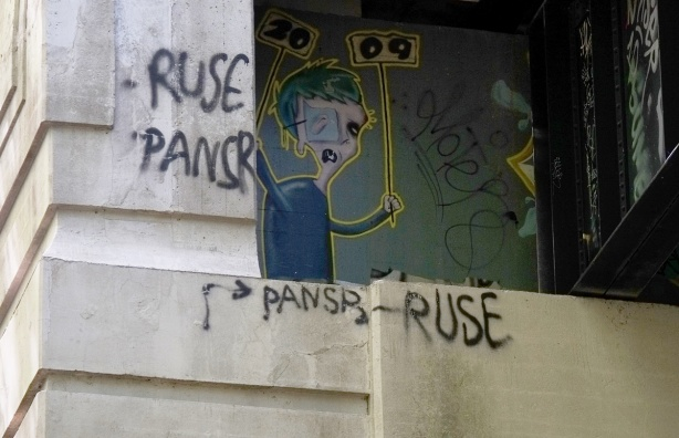 street art under a bridge with names pansr and use spray painted on