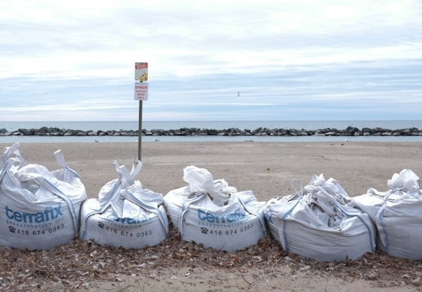 large white sandbags along the shore, beach on the other side, Lake Ontario in background with a row of rocks as breakwater a short distance from the shore, sign on the beach