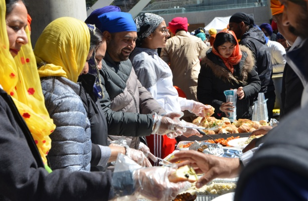 male and female volunteers serve food to people at khalsa celebrations.