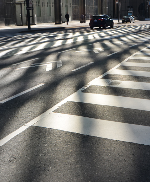 light and shadow patterns produce by low morning sun shining on downtown glass skyscrapers, on the street below with its white lines adding to the pattern