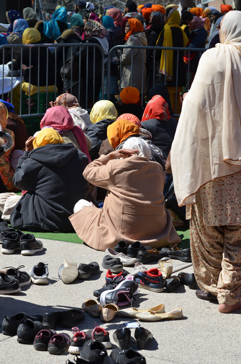 shoes inthe dorground, people sitting on a green mat, people standing in line waiting to pray beyond that