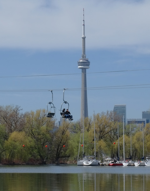 CN tower in the background, people on the Skyline ride at Centre Island passing over water, with large boats docked farther up the river