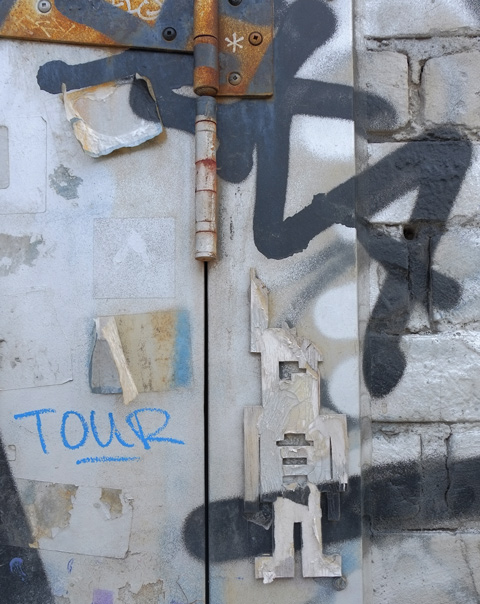 an old stikman on a wall by a door with a rusty hinge