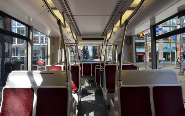 interior of a TTC streetcar, looking towards the back, red covered white seats, no one else on the car.