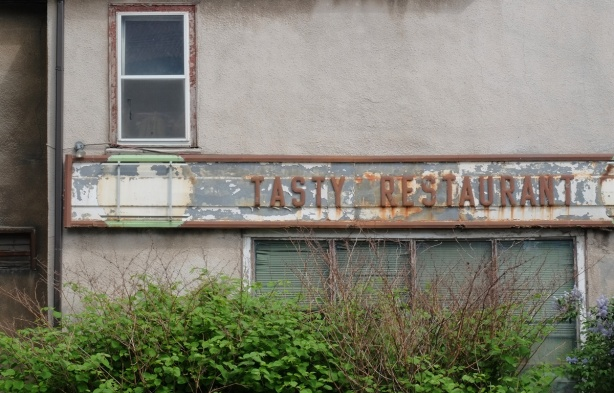 old rusty sign that says Tasty Restaurant. there is a round spot on the left where a coca-cola sign used to be, windows are overgrown by shrubs beside the building