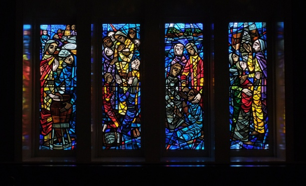 set of four stained glass windows in deep hues of red and blue with some yellow and green, by Gerald Tooke, at St Simons church