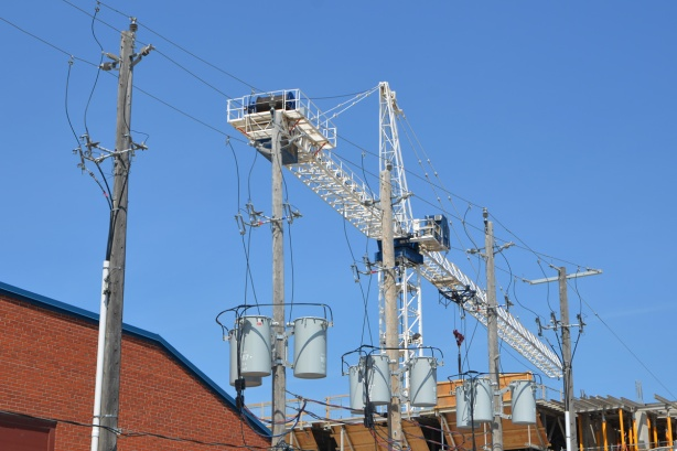 white crane in the background, many hydro utility poles, with large grey cylindrical transformers on each of them