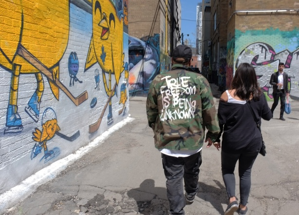 Graffiti alley, walking past an uber 5000 mural, a man and a woman with their backs to the camera. on the back of the man's camo coloured jacket are the words true freedom is being unknown