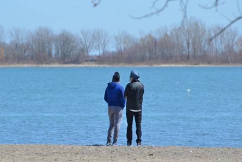 two sikh men in turbans stand on beach, early spring, wearing jackets and long pants.