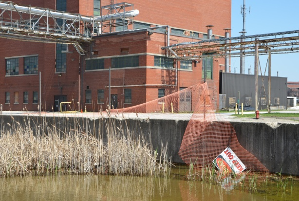 red brick large Unilever factory, with exterior pipes, brackish pond in the foreground, with orange plastic fence around it, part of fence has collapsed and Danger sign is near the water