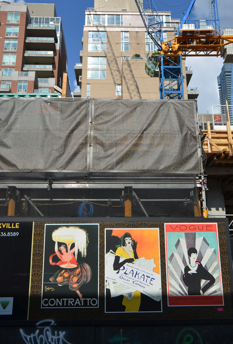 art deco posters on hoardings in front of a construction site inclujding a Vogue picture