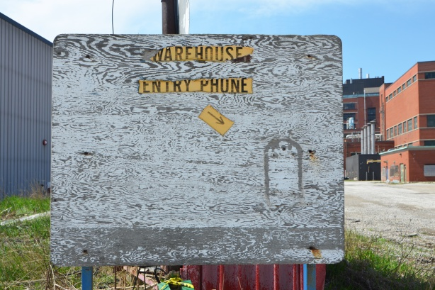 warehouse entry phone sign on white painted plywood where most of the white paint is gone, phone is not there, just the marks of where it used to be