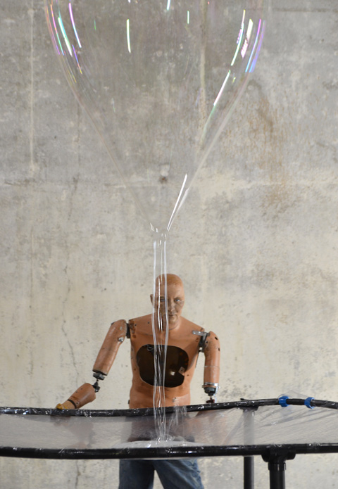 mannequin automatons as part of an art installation in the old Unilever soap factory, concrete floor and walls - solitary man with half an arm missing, staring straight ahead, beside a net to catch soap, a large soap bubble dropping from above him