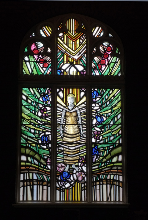 stained glass window by Stephen Taylor, memorial to the women of St. Simons, with a woman in the center, roots wrapped around her and greenery growing out from her,