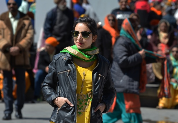 a young sikh woman stands in front of a crowd of people, yellow sari, black leather jacket and green and gold scarf around her neck