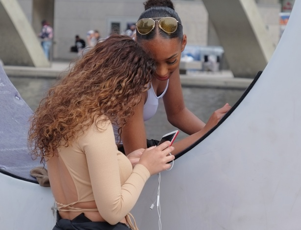 two women in the O of the 3D Toronto sign at Nathan Phillips square in front of city hall, examining photos that they have taken on their phone
