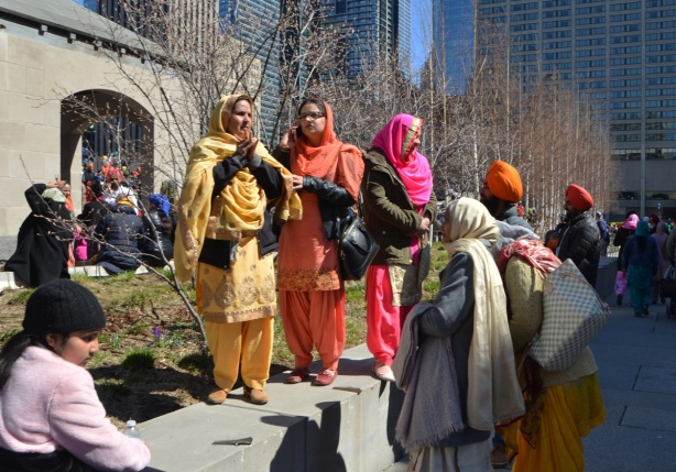 sikh women in pink, orange, and yellow saris, standing outside and socializing