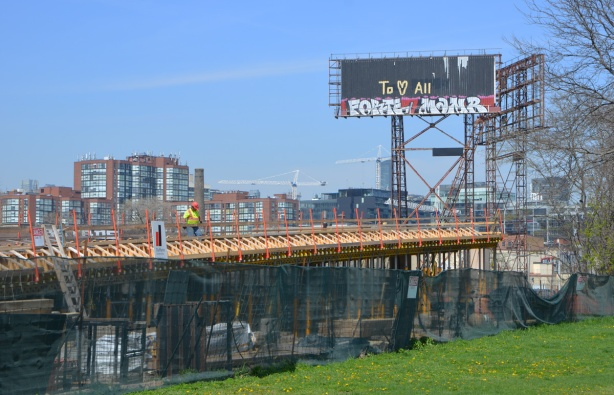 billboard beside construction of an elevated ramp beside a park