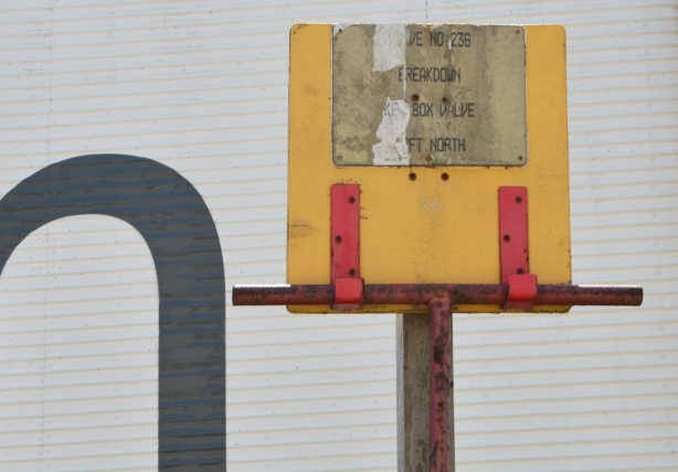 yellow wign held up by red metal brackets. faded sign,
