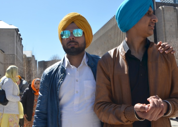 two young men in turbans, one blue and one yellow. one is wearing reflective sunglasses