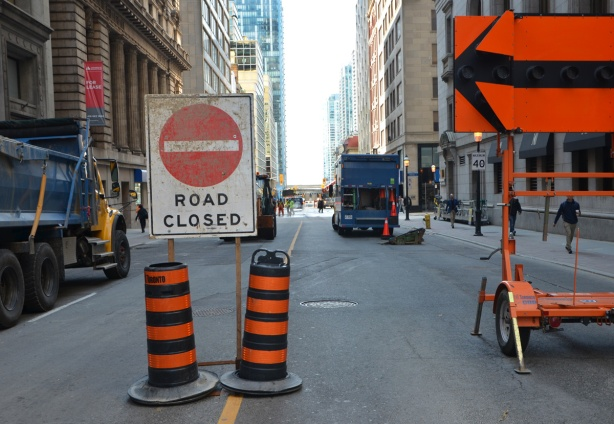 road closed sign, black arrow on orange sign, ornage and black striped traffic cones, blocking Yonge street, with trucks in the background.
