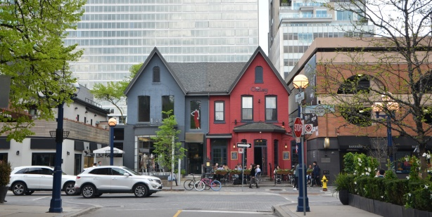looking down Hazelton Ave towards Yorkville Ave., two older houses, now used as commercial businesses, one half painted blue and the other half is red.
