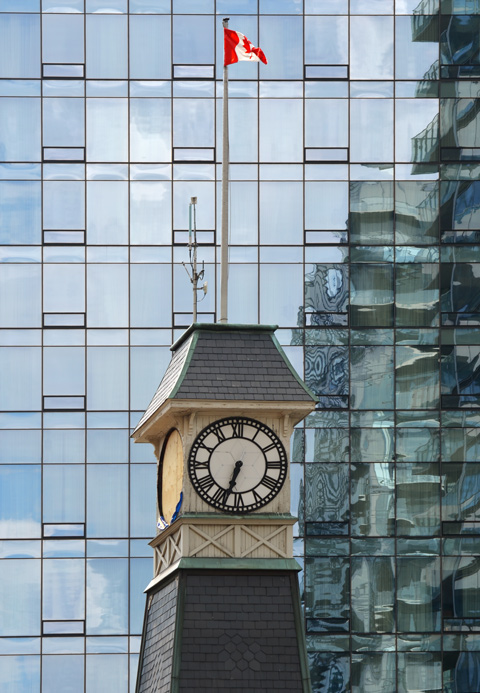 the clock tower of Yorkville fire station with a reflective glass building behind it. A Canadian flag is flying on top of the firehall clock tower.