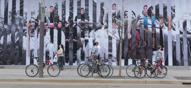 caroline Monnet's large mural on the side of TIFF building, King street, people walking past, bikes parked in front of the art.