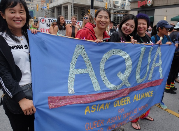 dyke march 2018 - Asian women holding a blue banner that says Aqua, Asian Queer Alliance, 5 women holding the banner
