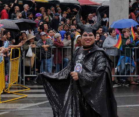 man in long black robes and hat with two black horns, walking in parade, crowds behind him,
