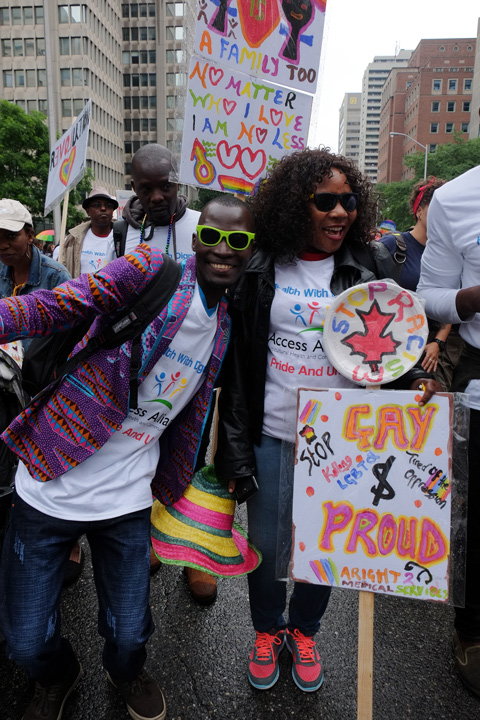 a black woman with long curly hair is holding three signs in bright colours while getting ready for the pride parade, the photo is photobombed by another black person with bright green sunglasses on