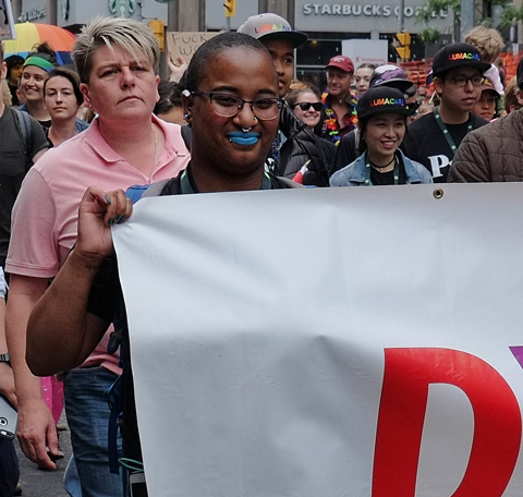 dyke march 2018 - dark brown person wearing blue lipstick holds a white banner