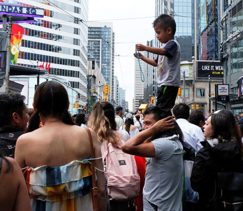 a boy on his father's shoulders, playing with a green bead necklace as they watch the pride parade in TOronto