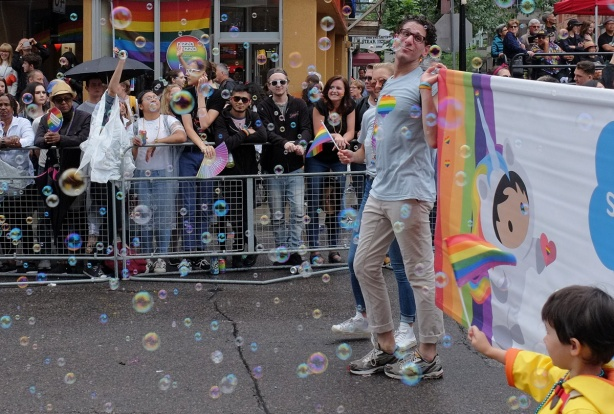lots of bubbles as people walk in pride parade, man holding a banner, boy in yellow jacket walking in front of banner