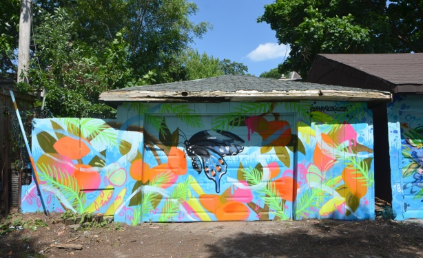 mural running horizontally across garage, garage door and adjoining fence, butterflies and flowers